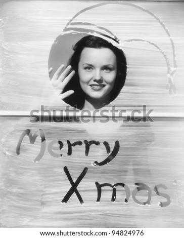 Woman waving at window with Christmas greeting - stock photo