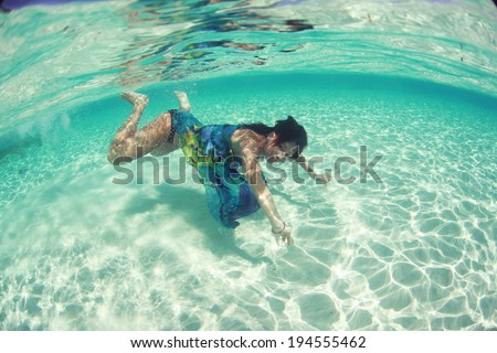 Woman wearing a blue dress and swimming in the ocean