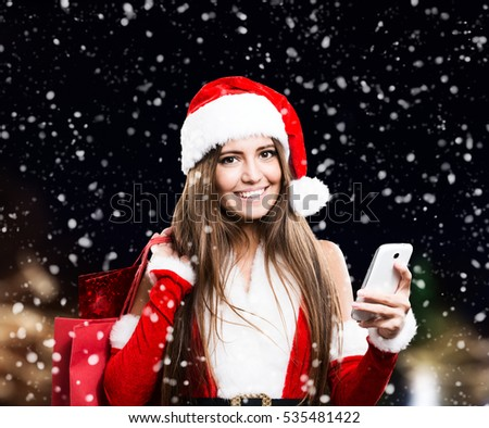 Woman wearing a Christmas dress using a mobile phone while the snow is falling