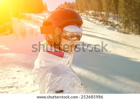 Woman wearing a helmet and glasses on the background of snow winter and mounts. - stock photo