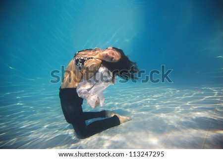 Woman wearing a jeans underwater in swimming pool