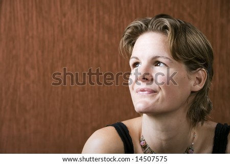 Woman wearing a necklace looking up to the left - stock photo