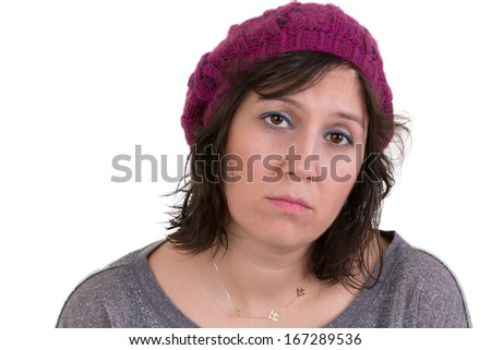 Woman wearing a purple beanie looking at the camera with a mournful woebegone expression and dull eyes, isolated on white - stock photo