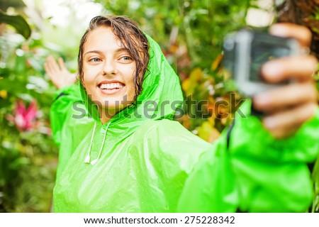woman wearing a raincoat taking selfie on a waterproof camera - stock photo