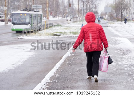 Woman wearing a red jacket throwing snow in the air in winter holidays
