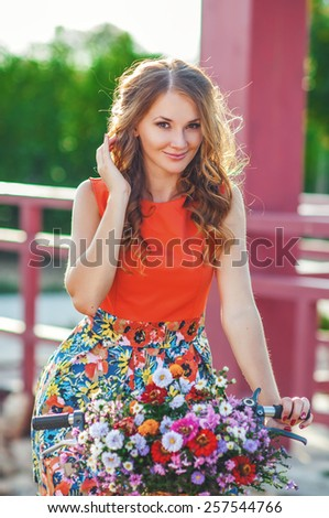 Woman wearing a spring skirt like vintage pin-up holding bicycle with some colorful flowers in the basket in old town - stock photo