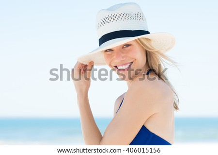 Woman wearing a straw hat and smiling. Portrait of a happy young woman in blue bikini with panama hat looking at camera with copy space. - stock photo