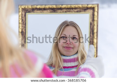 Woman wearing a warm sweater looking at her self at mirror and smiling. She likes her self. - stock photo