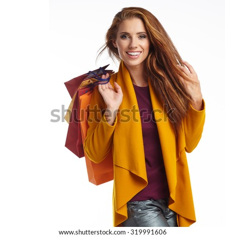 Woman wearing autumn overcoat holding shopping bag. - stock photo