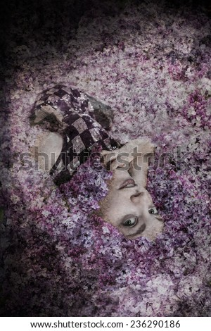 Woman wearing black and silver sequin dress lying in lilac flowers - stock photo