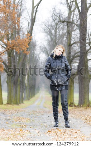 woman wearing black clothes and boots in autumnal alley - stock photo