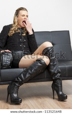 woman wearing black clothes and boots sitting on sofa