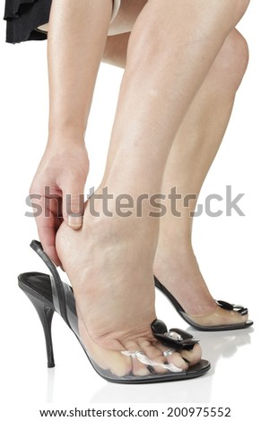Woman wearing black heel shoes massaging foot - stock photo