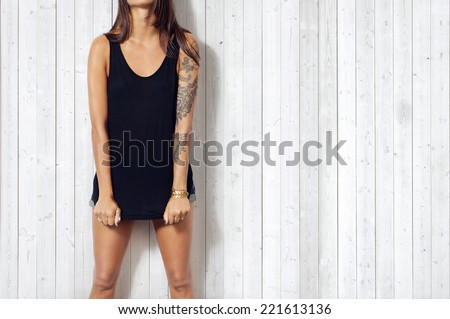 Woman wearing black vest. Wood wall background. - stock photo