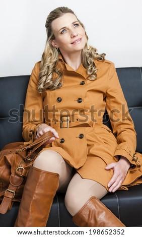 woman wearing brown coat sitting on sofa - stock photo