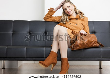 woman wearing brown coat with a handbag sitting on sofa - stock photo