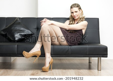 woman wearing brown pumps sitting on sofa - stock photo
