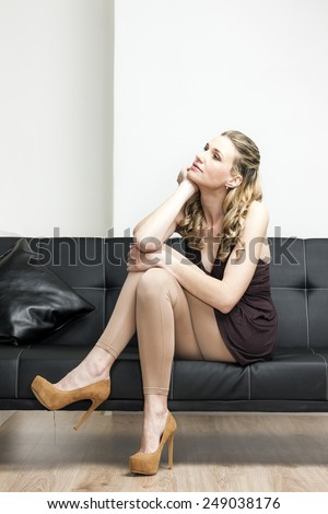 woman wearing brown pumps sitting on sofa