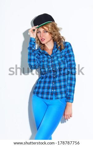 woman wearing cap posing near white wall - stock photo