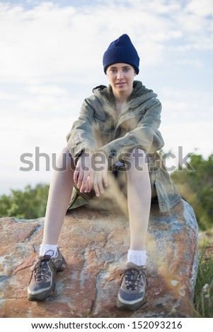 Woman wearing cap sitting on stone looking at camera - stock photo