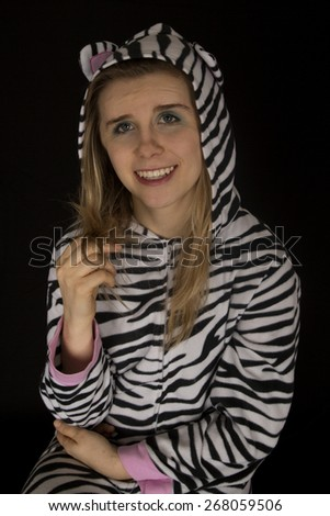 Woman wearing cat pajamas playing with hair - stock photo