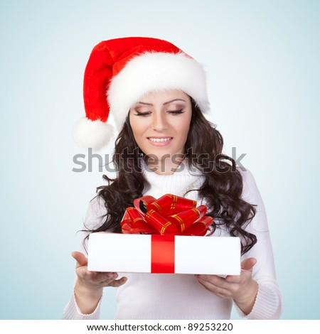 woman wearing christmas hat looking at gift box