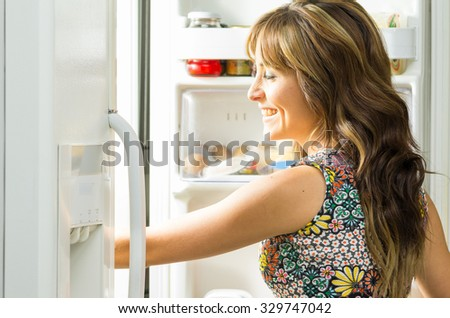 Woman wearing colorful dress in modern kitchen opening fridge door and reaching inside. - stock photo