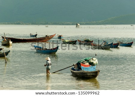 woman wearing conical hat with the fishing boats in lagoon - stock photo