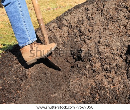 woman wearing denims and workbooks,digging in a pile of topsoil. image shows foot and part of leg. - stock photo
