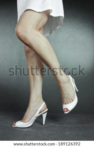 Woman wearing dress and white high heels over grey background - stock photo