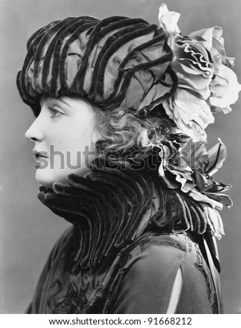 Woman wearing elaborate hat - stock photo
