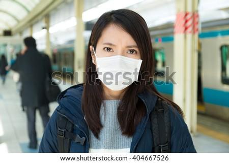 Woman wearing face mask at train platform - stock photo
