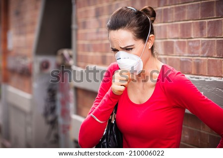 Woman wearing face-mask coughing - stock photo
