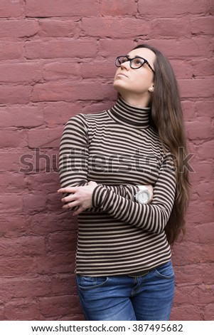Woman wearing fashionable clothing against a brick wall background
