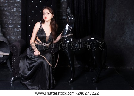 Woman Wearing Formal Black Dress Sitting Next to Dog Statue on Chain