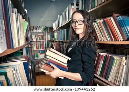 woman wearing glasses holding a pile of books - stock photo
