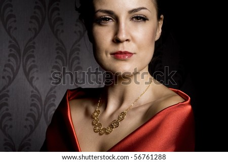 woman wearing golden necklace over wallpaper background - stock photo