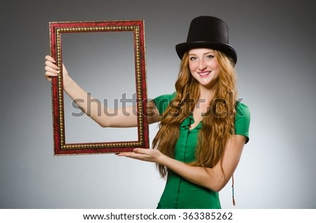 Woman wearing green dress holding picture frame - stock photo