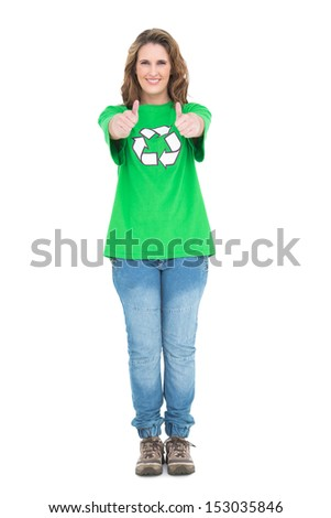 Woman wearing green tshirt with recycling symbol giving thumbs up on white background - stock photo