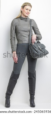 woman wearing grey clothes with a handbag - stock photo