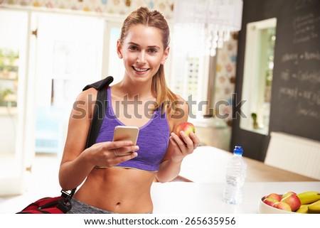 Woman Wearing Gym Clothing Choosing Fruit From Bowl - stock photo