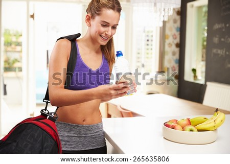 Woman Wearing Gym Clothing Looking At Mobile Phone - stock photo