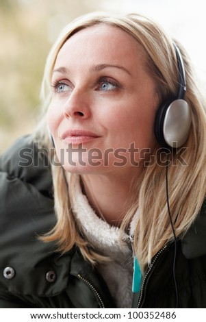 Woman Wearing Headphones And Listening To Music Wearing Winter Clothes - stock photo