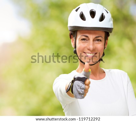 Woman Wearing Helmet Showing Thumb Up, Outdoor - stock photo