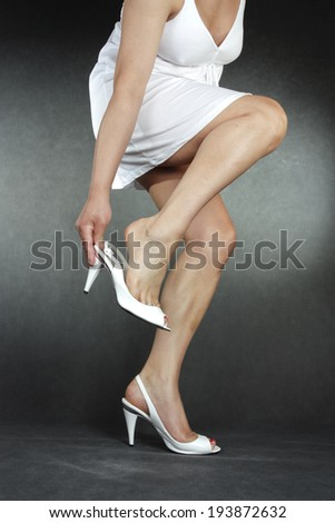 Woman wearing high heel shoes over grey background - stock photo