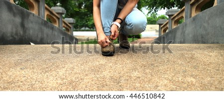 Woman wearing jeans Laced shoes sit on a bridge in the park. - stock photo