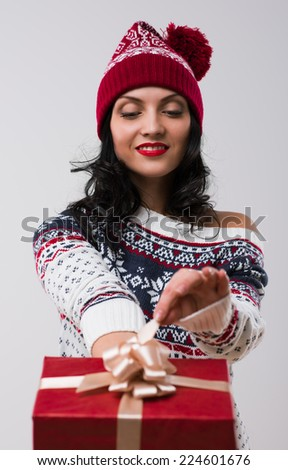 Woman wearing knitted winter dress and hat holding and opening Christmas gift - stock photo