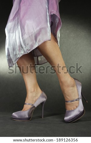 Woman wearing lilac satin dress and heels over grey background - stock photo