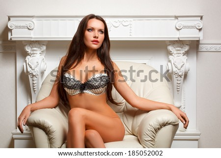 woman wearing lingerie sitting on leather sofa - stock photo