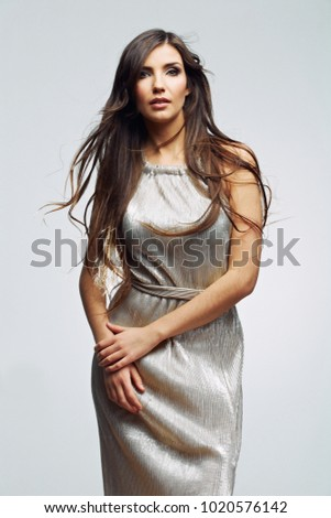 Woman wearing long evening dress. Studio isolated portrait on gray background .